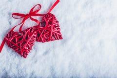 Deux coeurs rouges de beau vintage attachés ainsi qu'un ruban sur un fond blanc de neige Amour et concept de jour de valentines d Photo stock