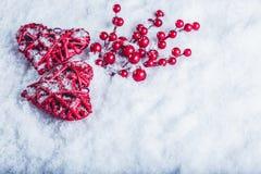 Deux coeurs rouges de beau vintage avec des baies de gui sur un fond blanc de neige Noël, amour et concept de jour de valentines  Images libres de droits