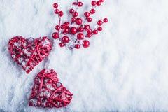 Deux coeurs rouges de beau vintage avec des baies de gui sur un fond blanc de neige Noël, amour et concept de jour de valentines  Photographie stock