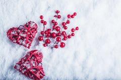 Deux coeurs rouges de beau vintage avec des baies de gui sur un fond blanc de neige Noël, amour et concept de jour de valentines  Image libre de droits