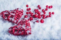 Deux coeurs rouges de beau vintage avec des baies de gui sur un fond blanc de neige Noël, amour et concept de jour de valentines  Images stock