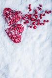 Deux coeurs rouges de beau vintage avec des baies de gui sur un fond blanc de neige Noël, amour et concept de jour de valentines  Photographie stock libre de droits