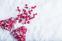 Deux coeurs rouges de beau vintage avec des baies de gui sur un fond blanc de neige Noël, amour et concept de jour de valentines  Photos libres de droits