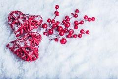 Deux coeurs rouges de beau vintage avec des baies de gui sur un fond blanc de neige Noël, amour et concept de jour de valentines  Photo libre de droits