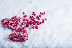 Deux coeurs rouges de beau vintage avec des baies de gui sur un fond blanc de neige Noël, amour et concept de jour de valentines  Photo stock