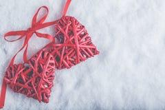 Deux coeurs rouges de beau vintage romantique attachés ainsi que le ruban sur le fond blanc de neige Amour et concept de jour de  Image stock
