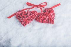 Deux coeurs rouges de beau vintage romantique attachés ainsi que le ruban sur le fond blanc de neige Amour et concept de jour de  Photo libre de droits