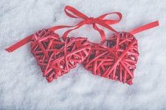 Deux coeurs rouges de beau vintage romantique attachés ainsi que le ruban sur le fond blanc de neige Amour et concept de jour de  Images stock