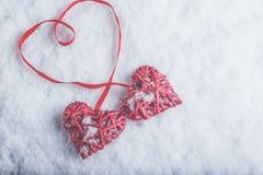 Deux coeurs rouges de beau vintage romantique attachés ainsi que le ruban sur le fond blanc de neige Amour et concept de jour de  Photographie stock libre de droits