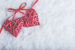 Deux coeurs rouges de beau vintage romantique attachés ainsi que le ruban sur le fond blanc de neige Amour et concept de jour de  Images libres de droits