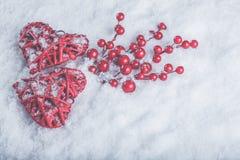 Deux coeurs rouges de beau vintage romantique avec des baies de gui sur la neige blanche Noël, amour et concept de jour de valent Photo libre de droits