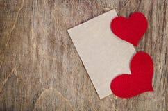 Deux coeurs rouges de tissu avec la feuille de papier Photos stock