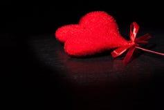 Deux coeurs rouges de velours décoratif sur la lumière foncée noire et sur la table en bois, concept de Saint Valentin Photo stock