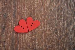Deux coeurs rouges en bois sur le panneau en bois Photos stock