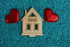 Deux coeurs rouges et une petite maison modèlent sur le sable bleu Image libre de droits