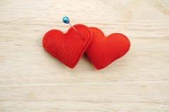 Deux coeurs rouges goupillés sur le fond en bois Images stock