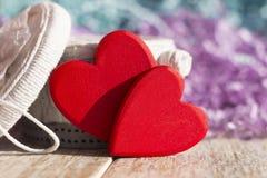 Deux coeurs rouges lumineux sur une boîte blanche de fond de papier fait main et de tresse colorée Photographie stock