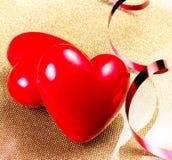Deux coeurs rouges sur la fin d'or de plat. Backgrou de jour de valentines Photographie stock