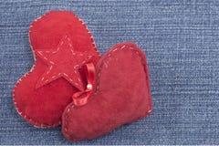 Deux coeurs rouges sur le fond de denim Images libres de droits
