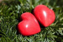 Deux coeurs rouges sur le fond des branches de sapin Jour de Valentine Photographie stock