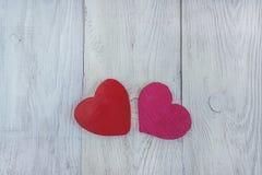 Deux coeurs rouges sur le fond en bois blanc Images stock