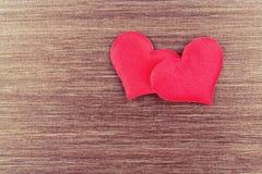 Deux coeurs rouges sur un conseil en bois Photos stock