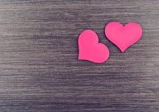 Deux coeurs rouges sur un conseil en bois Photographie stock
