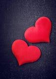 Deux coeurs rouges sur un conseil noir Photos libres de droits