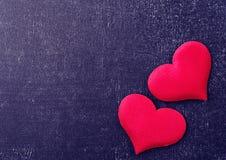 Deux coeurs rouges sur un conseil noir Images libres de droits