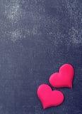 Deux coeurs rouges sur un conseil noir Photo stock