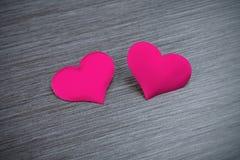 Deux coeurs rouges sur un conseil noir Photo libre de droits
