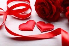 Deux coeurs, ruban et roses rouges sur la table Photos libres de droits