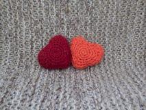 Deux coeurs se sont reliés de la laine sur un fond gris Photos libres de droits