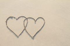 Deux coeurs sur la plage avec l'ombre molle, envoyant le concept d'amour Photographie stock libre de droits