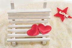 Deux coeurs sur un banc en bois miniature Photos stock