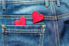 Deux coeurs sur un fond d'un plan rapproché de poche de jeans valentines Photo stock