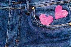 Deux coeurs sur un fond d'un plan rapproché de poche de jeans valentines Photographie stock libre de droits