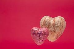 Deux coeurs sur un fond rouge Photos libres de droits