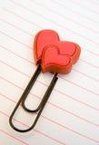Deux coeurs sur un trombone sur le papier de note rayé. Photographie stock libre de droits