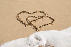 Deux coeurs sur une plage avec une vague entrante Image libre de droits