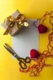 Deux coeurs tricotés, boîte-cadeau sur le fond jaune Photographie stock libre de droits