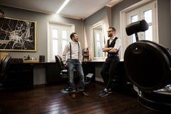Deux coiffeurs parlant dans le salon photographie stock