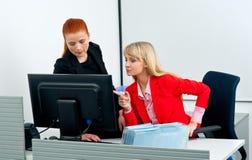 Deux colegues de femme travaillant sur l'ordinateur dans le bureau photographie stock libre de droits