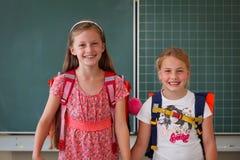Deux écolières dans le concept éducatif de salle de classe Photo stock