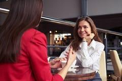 Deux collègues buvant du café et appréciant la conversation gentille du photo libre de droits