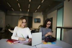 Deux collègues d'affaires résolvent leurs tâches du travail utilisant l'Internet gratuit et les dispositifs modernes Image stock