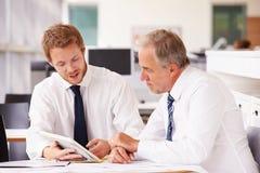 Deux collègues d'entreprise constituée en société travaillant ensemble dans le bureau images libres de droits