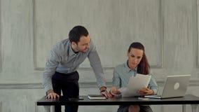 Deux collègues discutent autour de l'ordinateur portable banque de vidéos
