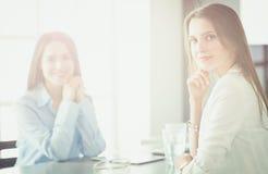 Deux collègues féminins dans le bureau se reposant sur le bureau photographie stock