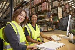 Deux collègues féminins dans un bureau d'entrepôt regardent à l'appareil-photo image stock
